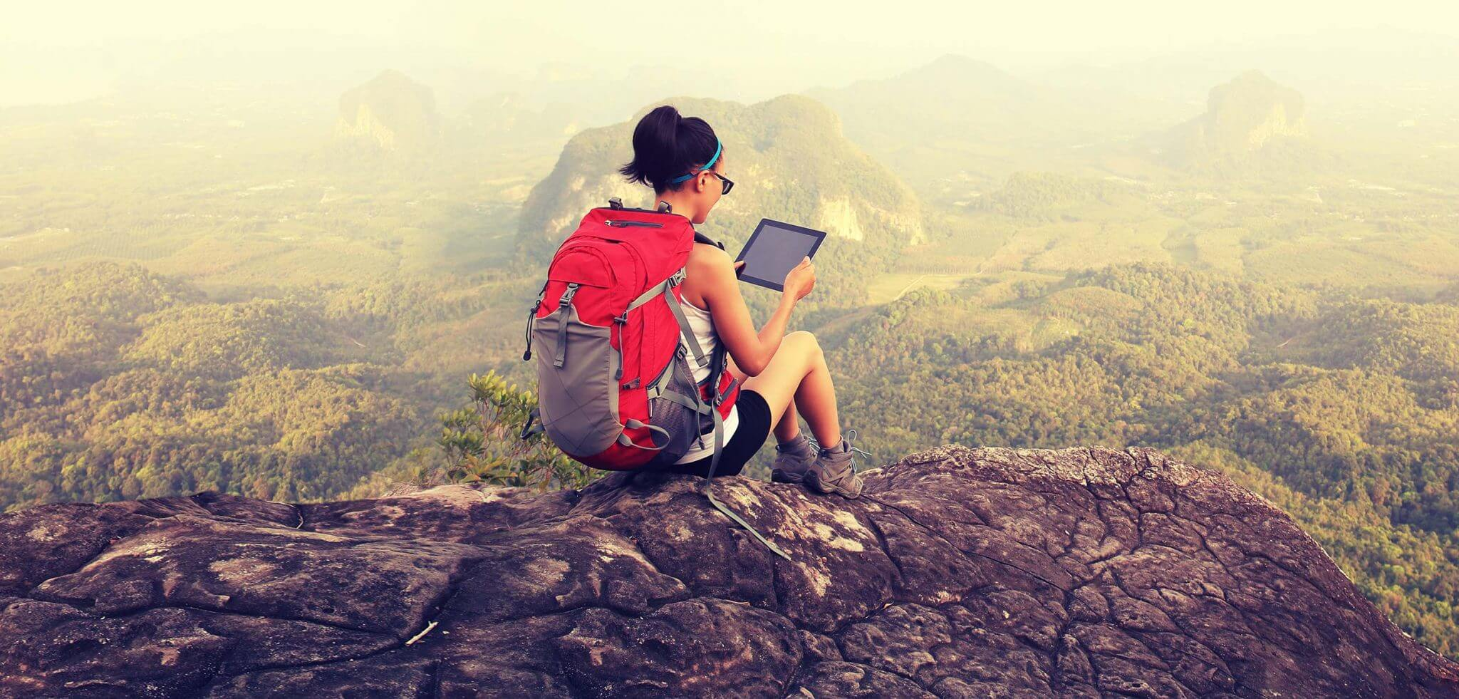 Woman on top of a hill with an ipad